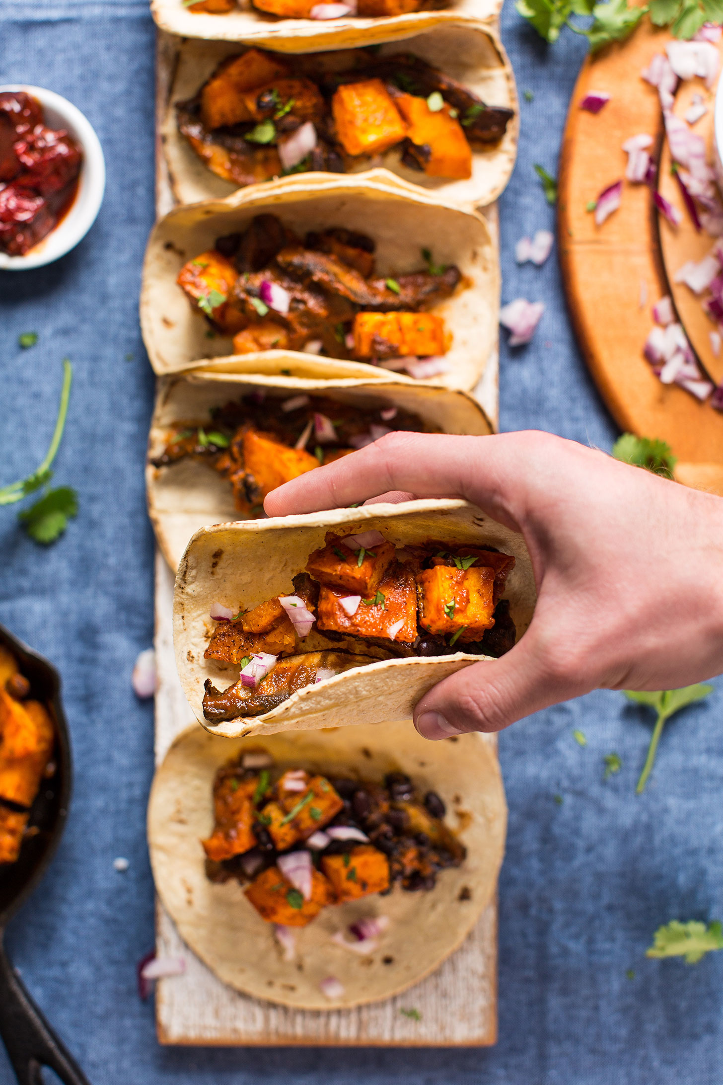 Holding up a Saucy Butternut Squash and Portobello Taco for a healthy gluten-free plant-based meal