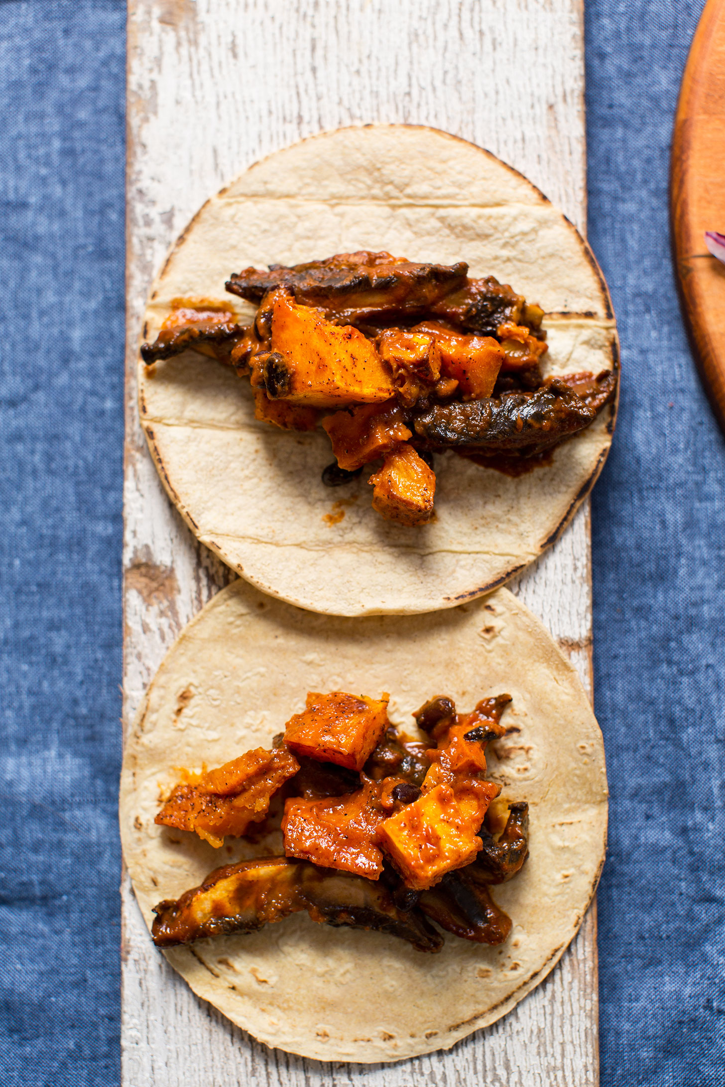 Wood plank displaying saucy gluten-free vegan Butternut Squash Tacos
