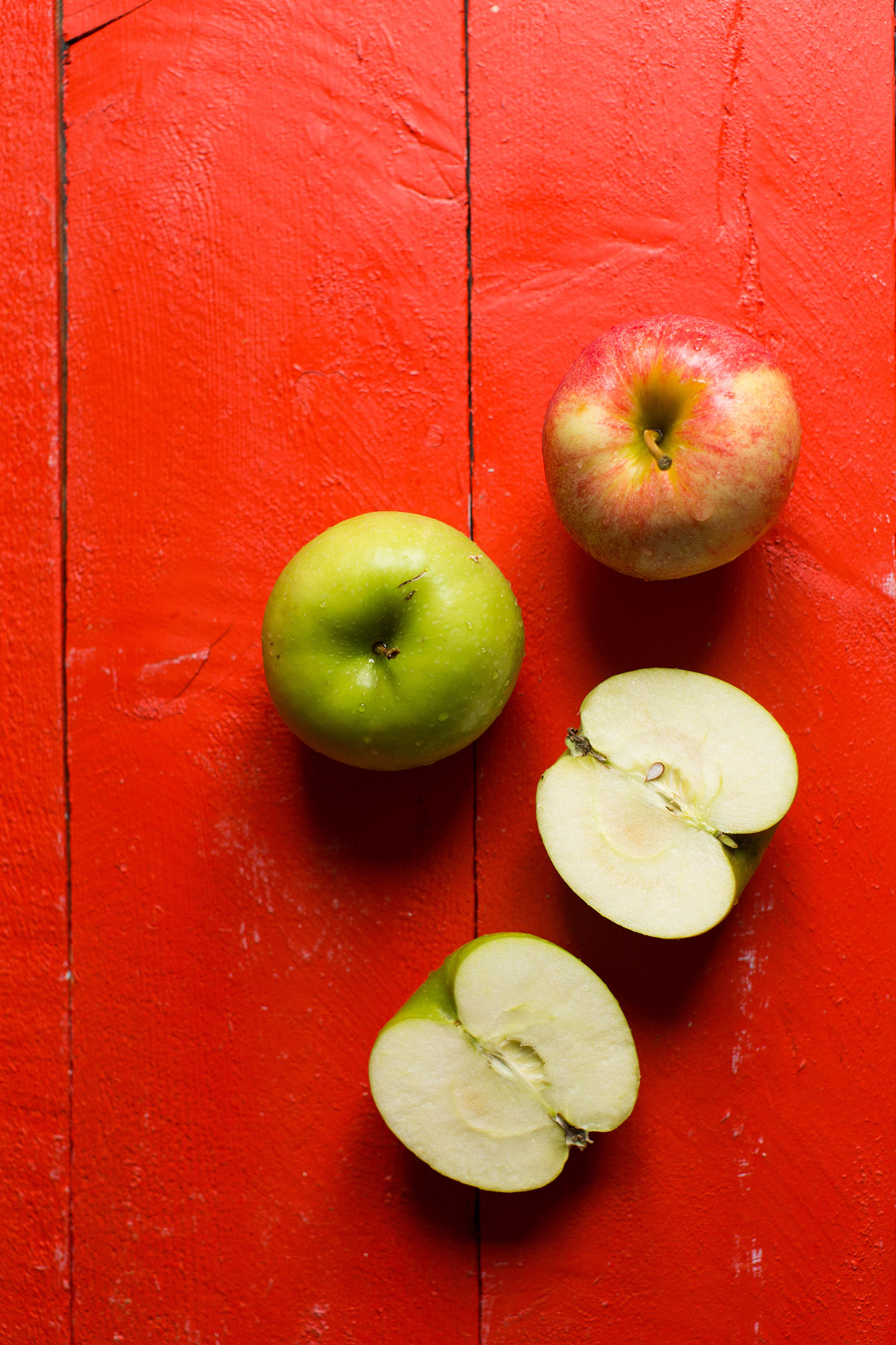 Fresh apples on a red background for a gluten-free vegan apple pie crumble bars recipe