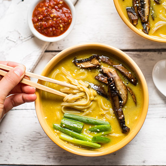 Using chopsticks to pick up a bite of delicious Coconut Curry Ramen