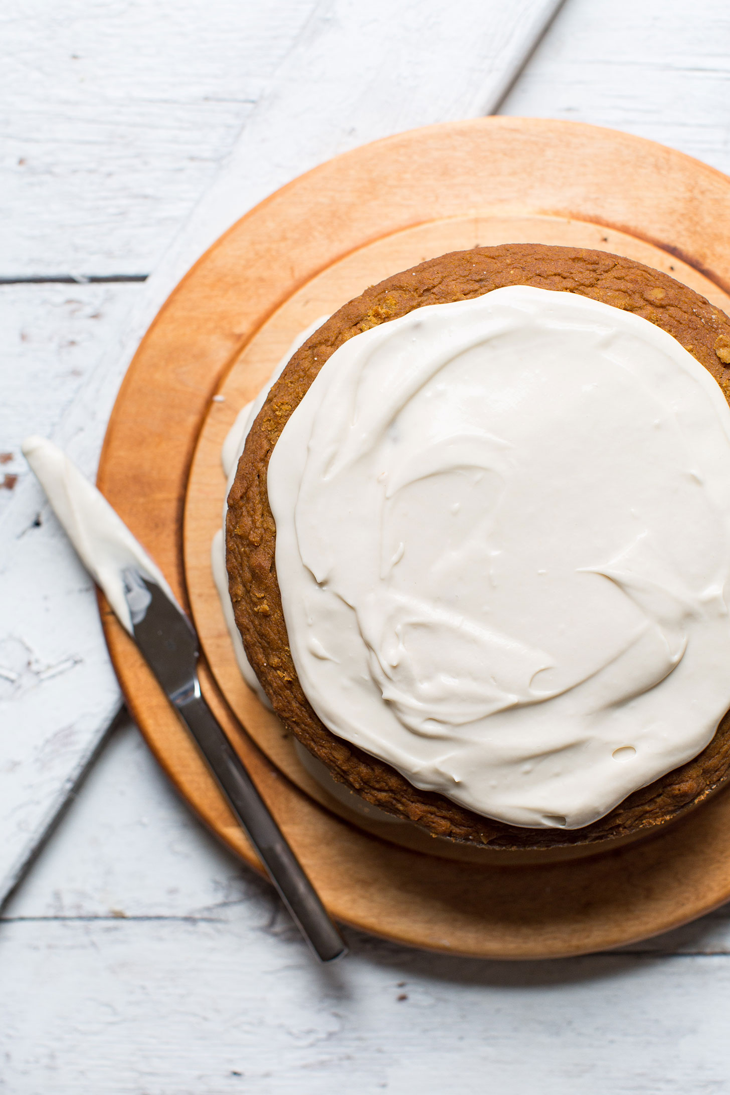 Spreading homemade vegan frosting onto our gluten-free Pumpkin Cake
