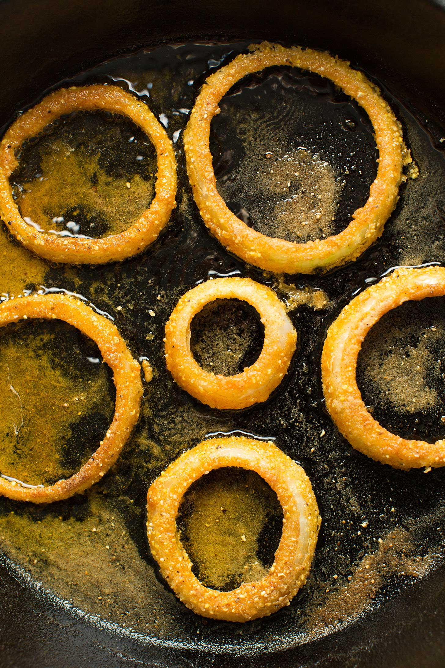 Gluten-free onion rings sizzling in a cast iron skillet