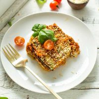 Plate with a slice of Lentil & Eggplant Lasagna topped with fresh basil