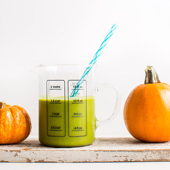 Pumpkins on a wood plank beside a measuring glass of our Pumpkin Pie Green Smoothie recipe