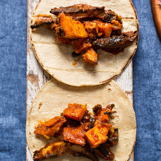 Two Portobello & Butternut Squash Tacos on a wood plank