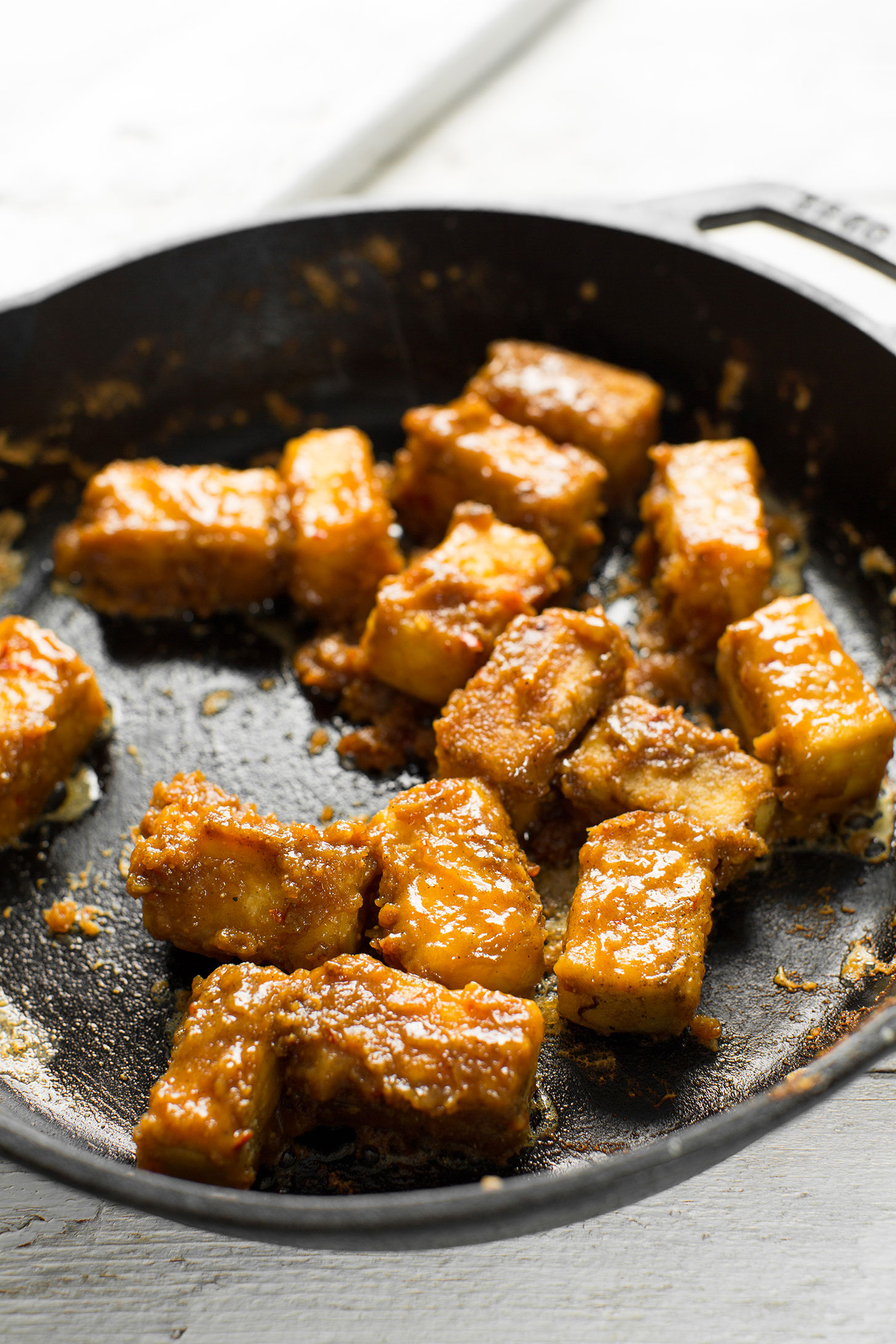 Cooking Almond Butter Tofu in a cast-iron skillet for a protein-packed plant-based meal