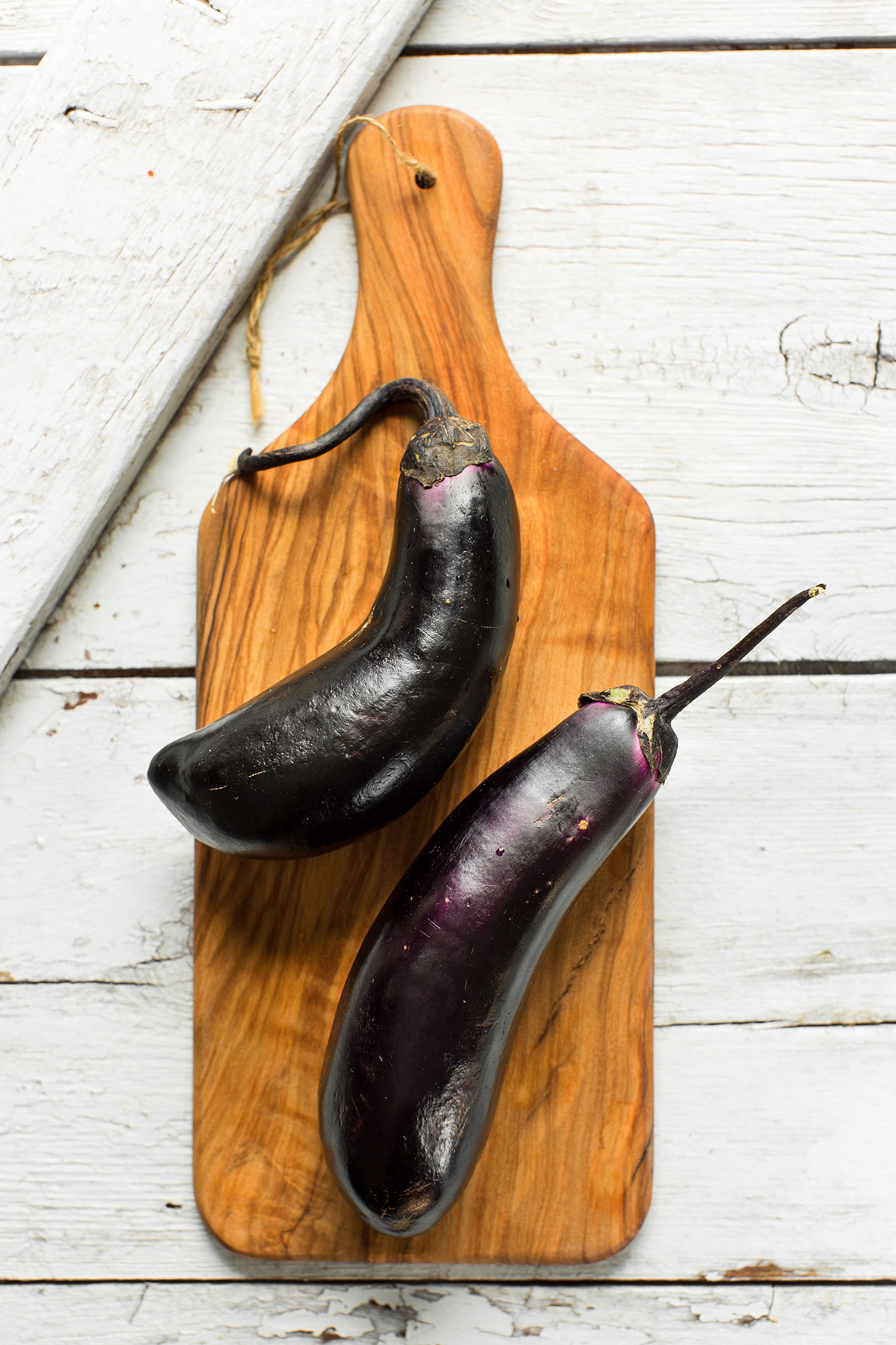 Fresh eggplants on a cutting board ready to be made into Sesame Stir-Fried Eggplant