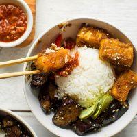 Using chopsticks to pick up a piece of Sesame Tofu