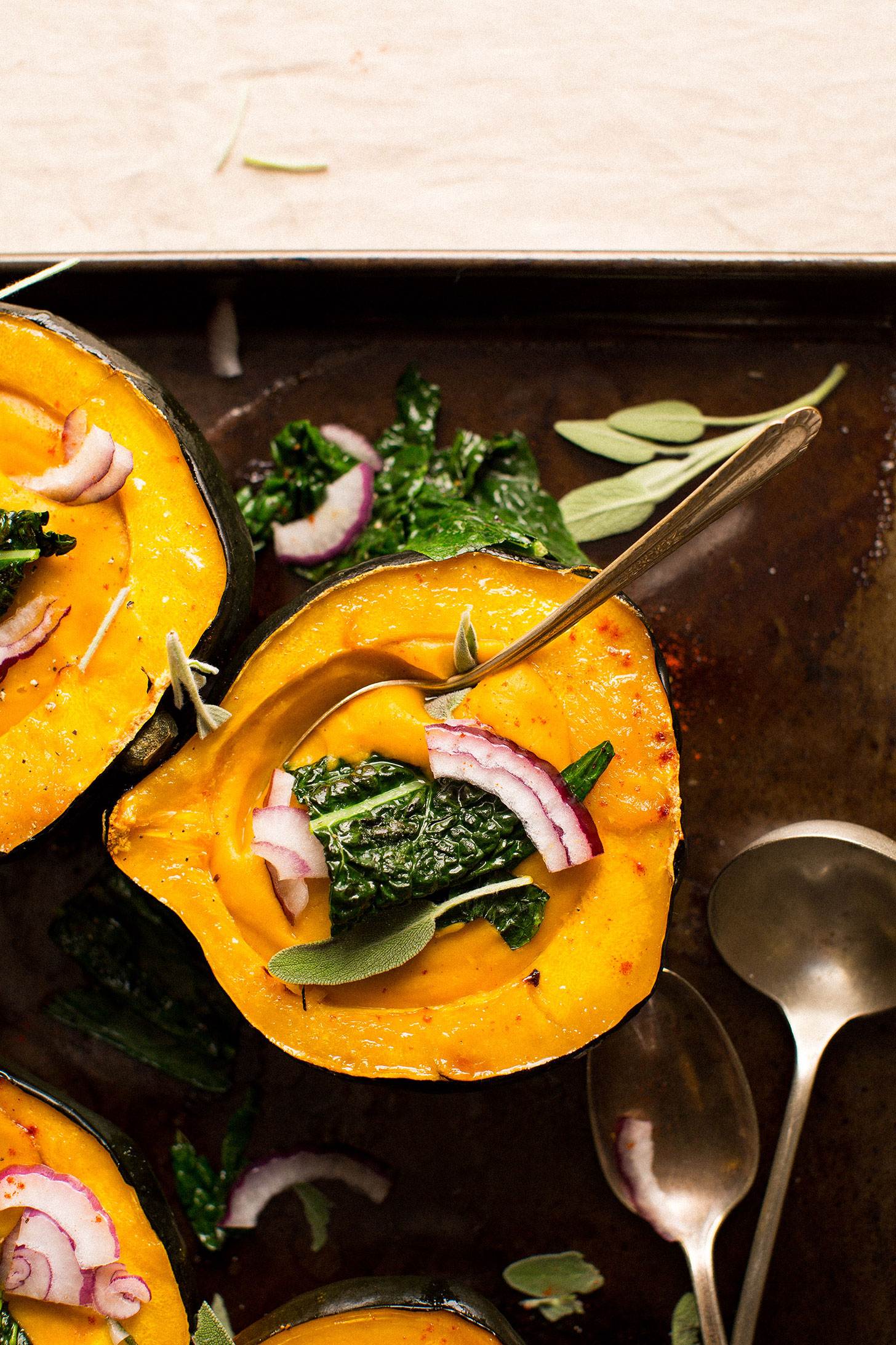 Grabbing a spoonful of gluten-free vegan Acorn Squash Soup from a squash bowl