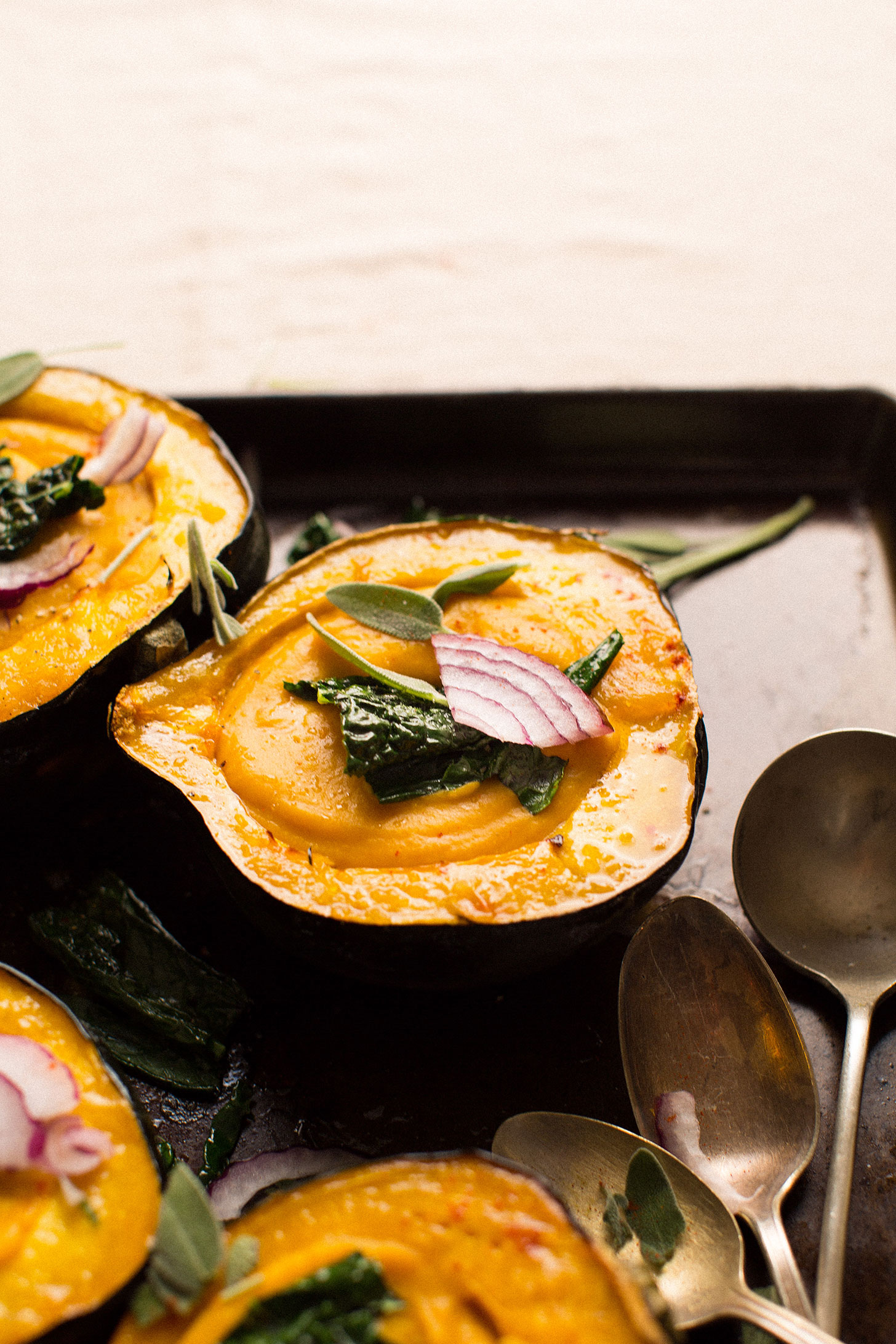 Acorn squash halves filled with squash soup and topped with onions, kale, and sage leaves