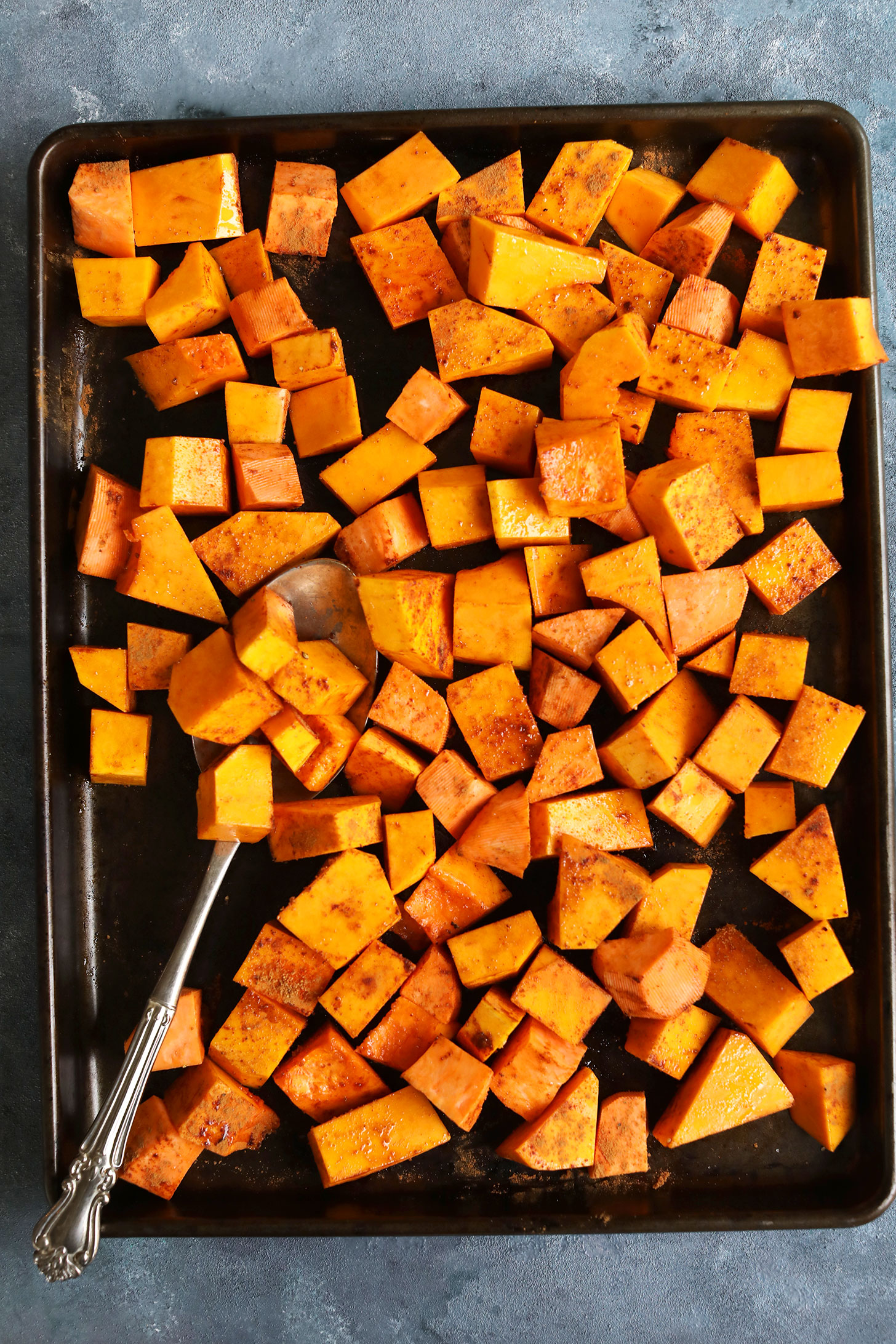 Baking sheet with cubed butternut squash for making a gluten-free vegan thanksgiving salad recipe