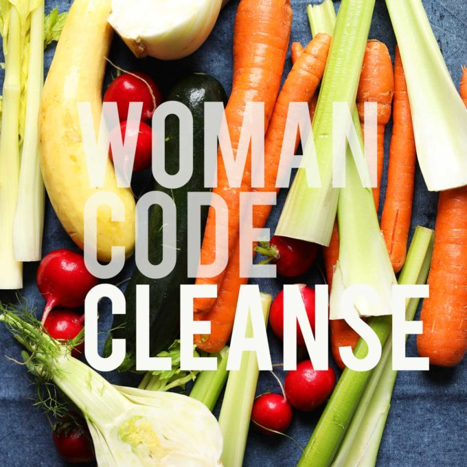 Woman Code Cleanse written over an assortment of fresh vegetables