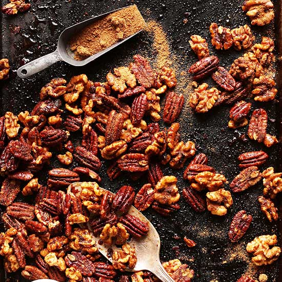 Baking sheet with a scoop of coconut sugar and batch of Candied Spiced Nuts