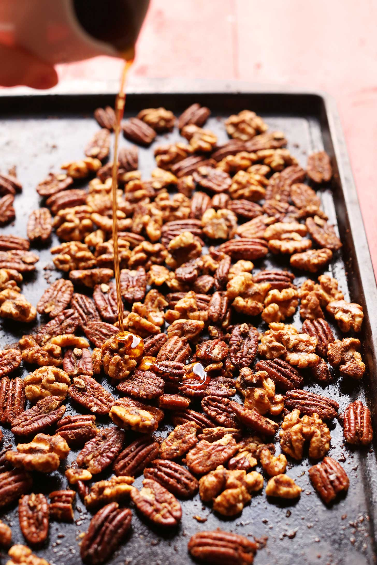 Pouring syrup onto nuts for our homemade holiday gift idea of Roasted Candied Nuts