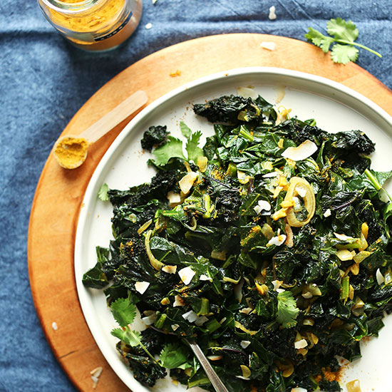 Big plate of Coconut Curried Greens beside a spoonful of curry powder