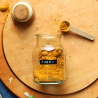 Spoonful and jar of our DIY Curry Powder