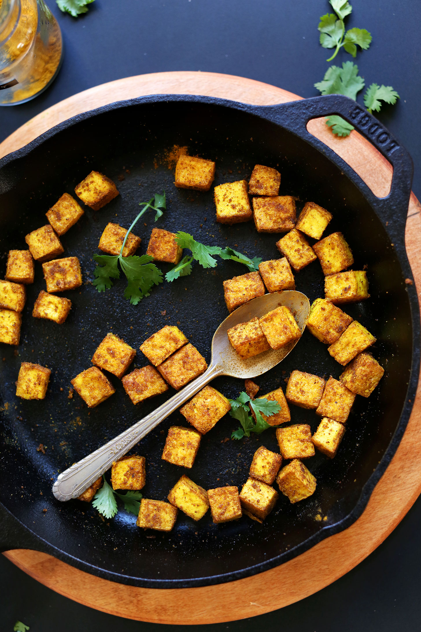 Grabbing a spoonful of Crispy Tofu from a skillet for an easy plant-based meal