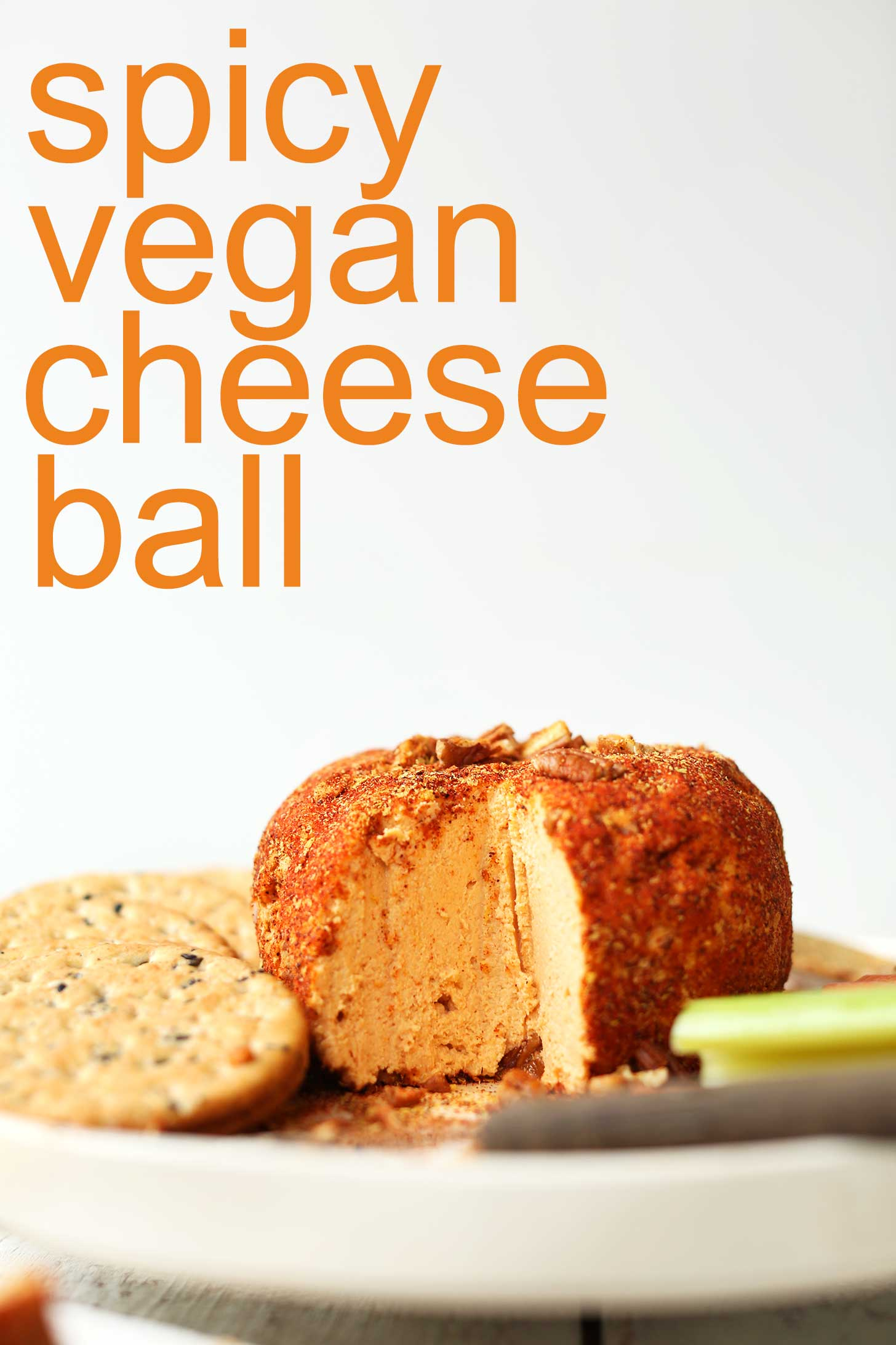 Spicy Vegan Cheese Ball on a plate with crackers and veggies for a holiday appetizer