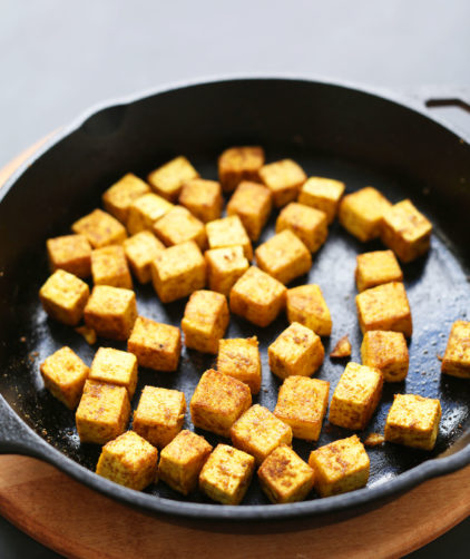 Cast iron skillet filled with cubes of tofu for quick and easy Crispy Tofu
