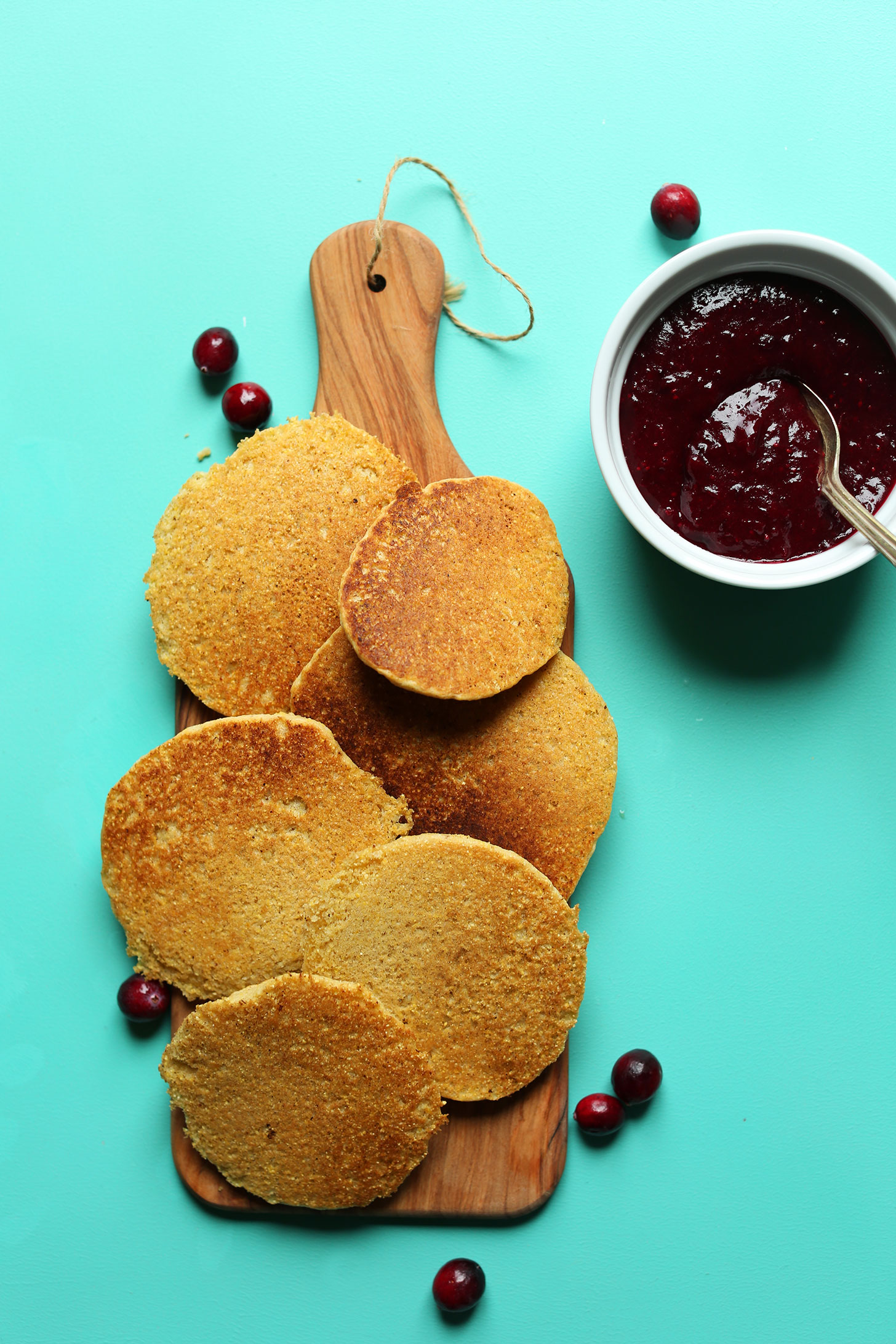 Wood cutting board with freshly made gluten-free cornmeal pancakes and a bowl of Cranberry Compote