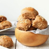 Bowl and tray of Fluffy Vegan Spelt Rolls topped with oats