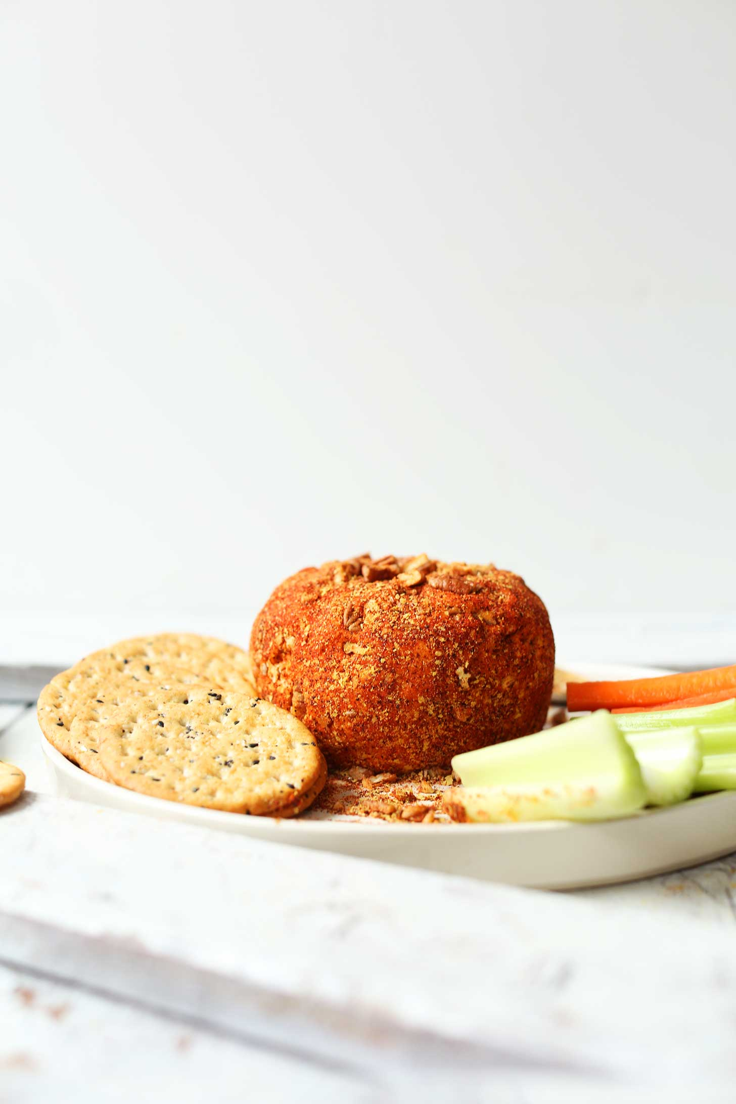 Crackers, veggie sticks, and a Spicy Vegan Cheese Ball for the perfect holiday appetizer