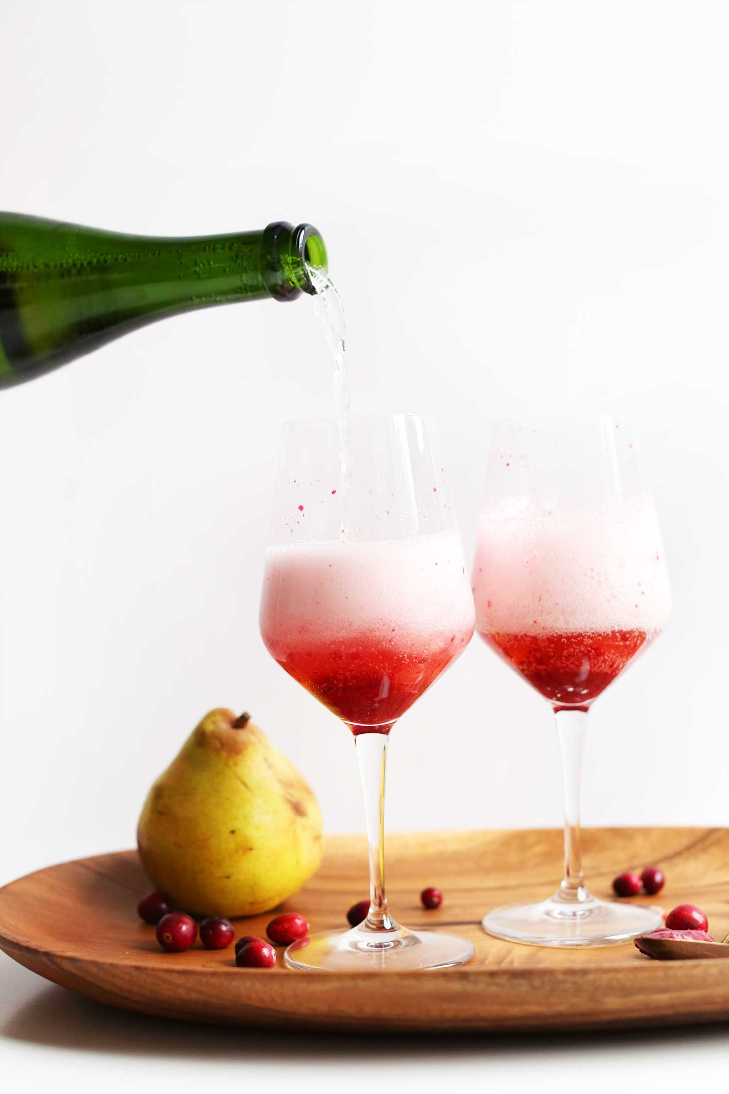Pouring champagne for our 5-Ingredient Champagne Mimosas with Cranberry-Pear Reduction