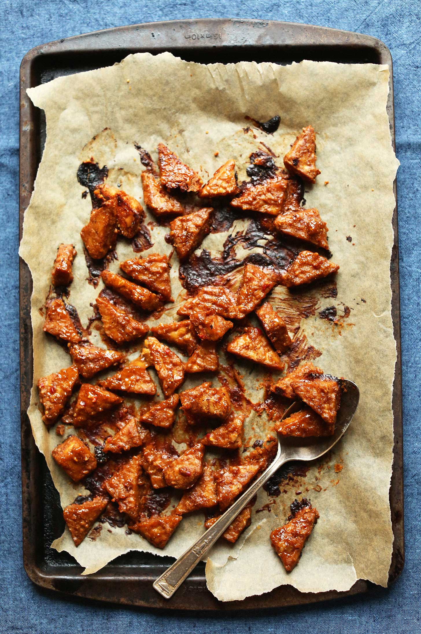 Parchment-lined baking sheet filled with our Marinated Peanut Baked Tempeh recipe