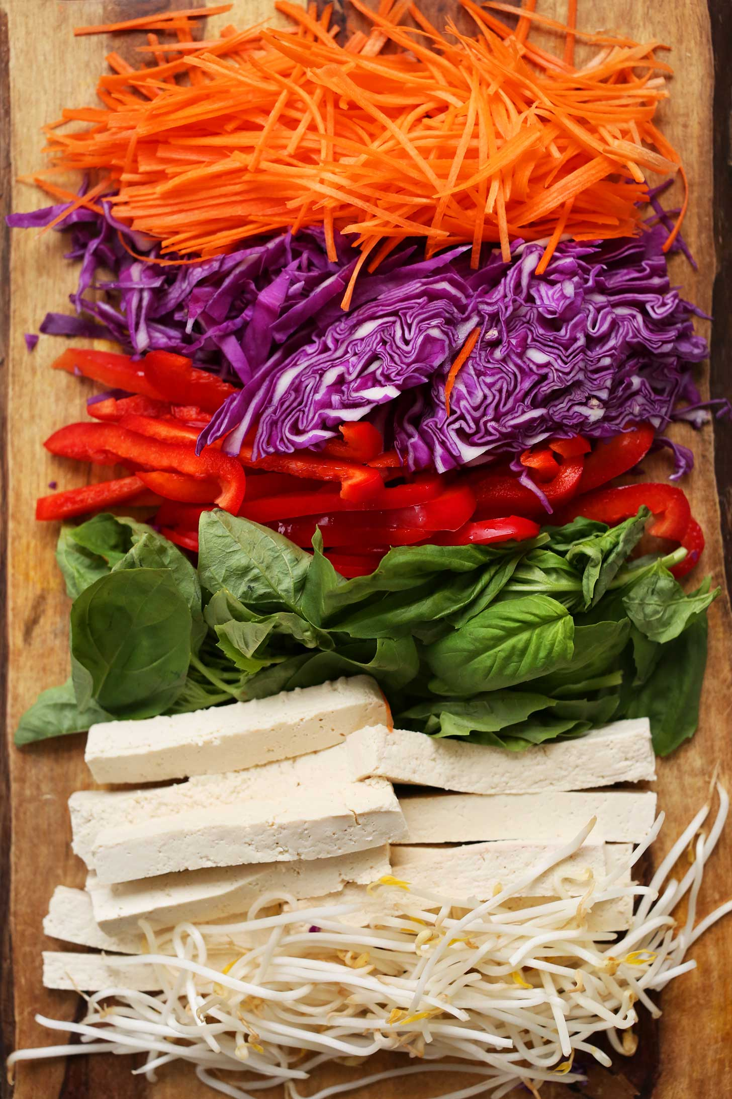 Shredded carrots, cabbage, bell pepper, basil, tofu, and bean sprouts for making homemade vegan salad rolls
