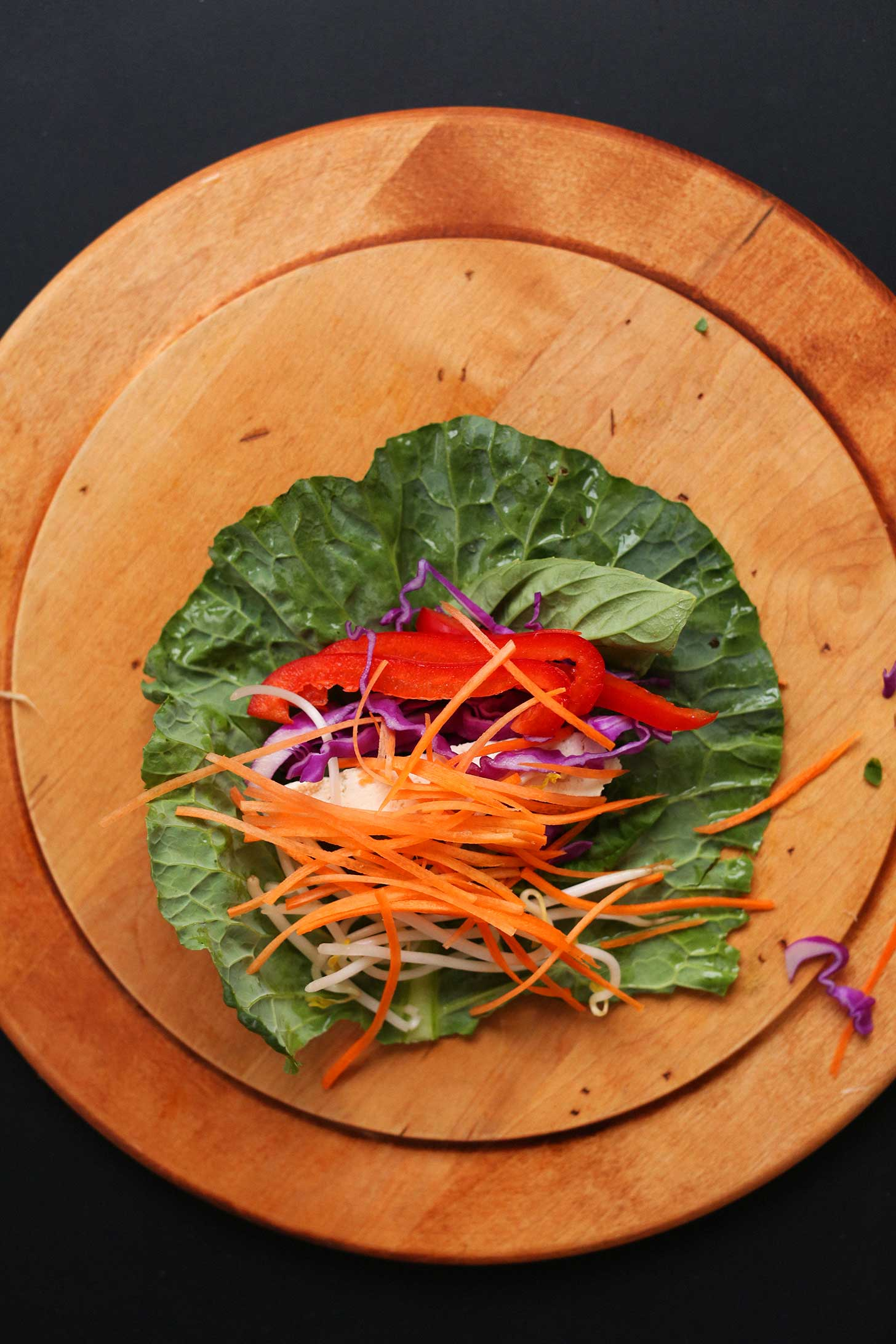 Wood cutting board with a collard green leaf and fresh ingredients for making hearty plant-based spring rolls