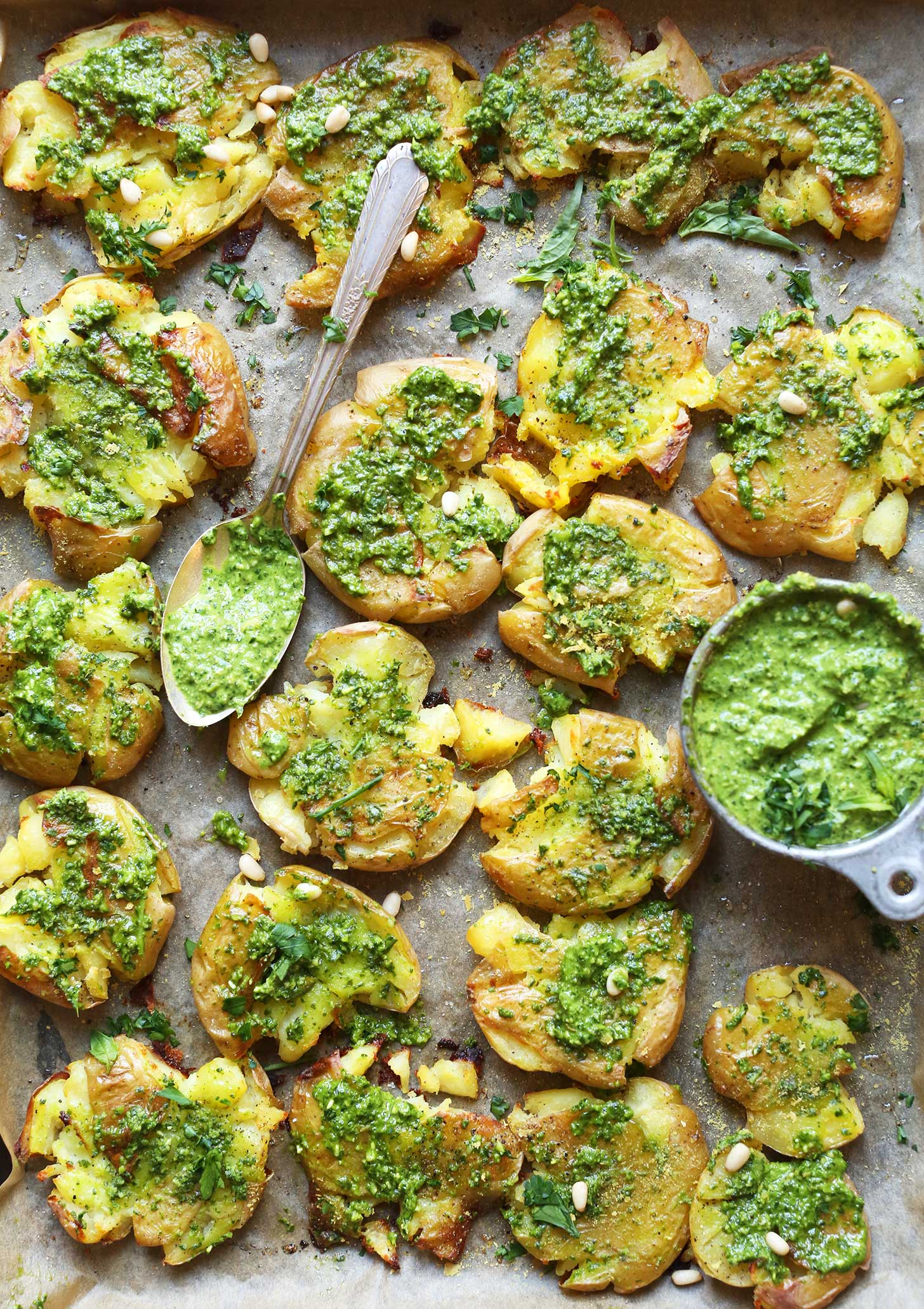 Parchment-lined baking sheet full of Smashed Potatoes smothered with vegan Garlic Herb Pesto