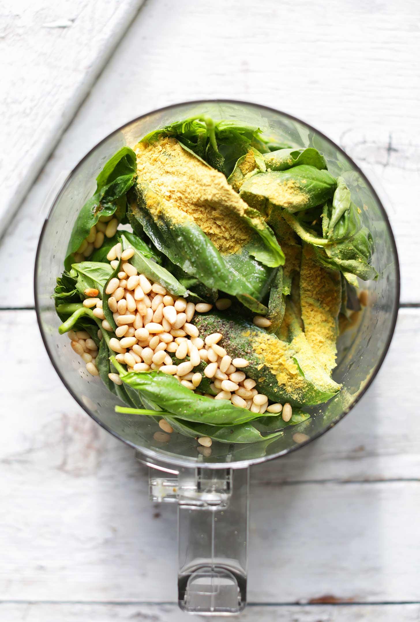 Food processor with ingredients for vegan Garlic Herb Pesto