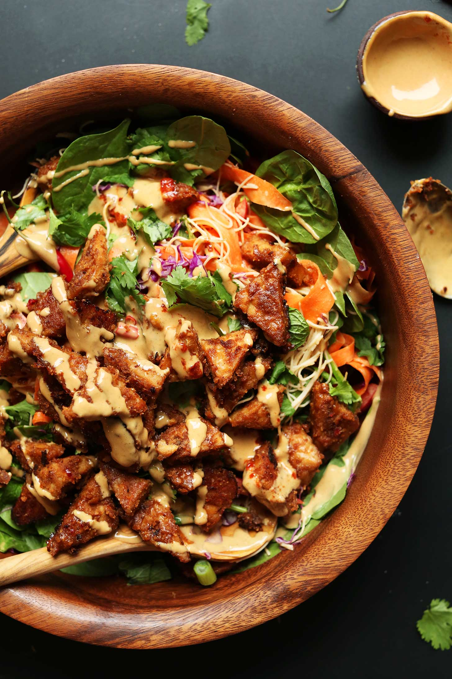 Beautiful wood bowl full of Thai Salad with Marinated Peanut Tempeh topped with our easy peanut sauce recipe