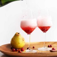 Fresh pears and cranberries on a platter with stemware filled with our Champagne Cocktails recipe
