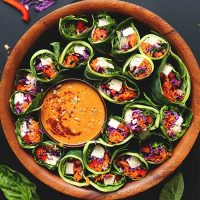 Collard Green Spring Rolls in a wood bowl with dipping sauce