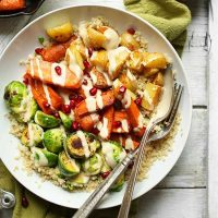 Spoon and fork in a Quinoa Harvest Bowl made with roasted vegetables and tahini sauce