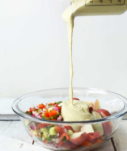 Pouring dressing onto our delicious vegetable-packed potato salad