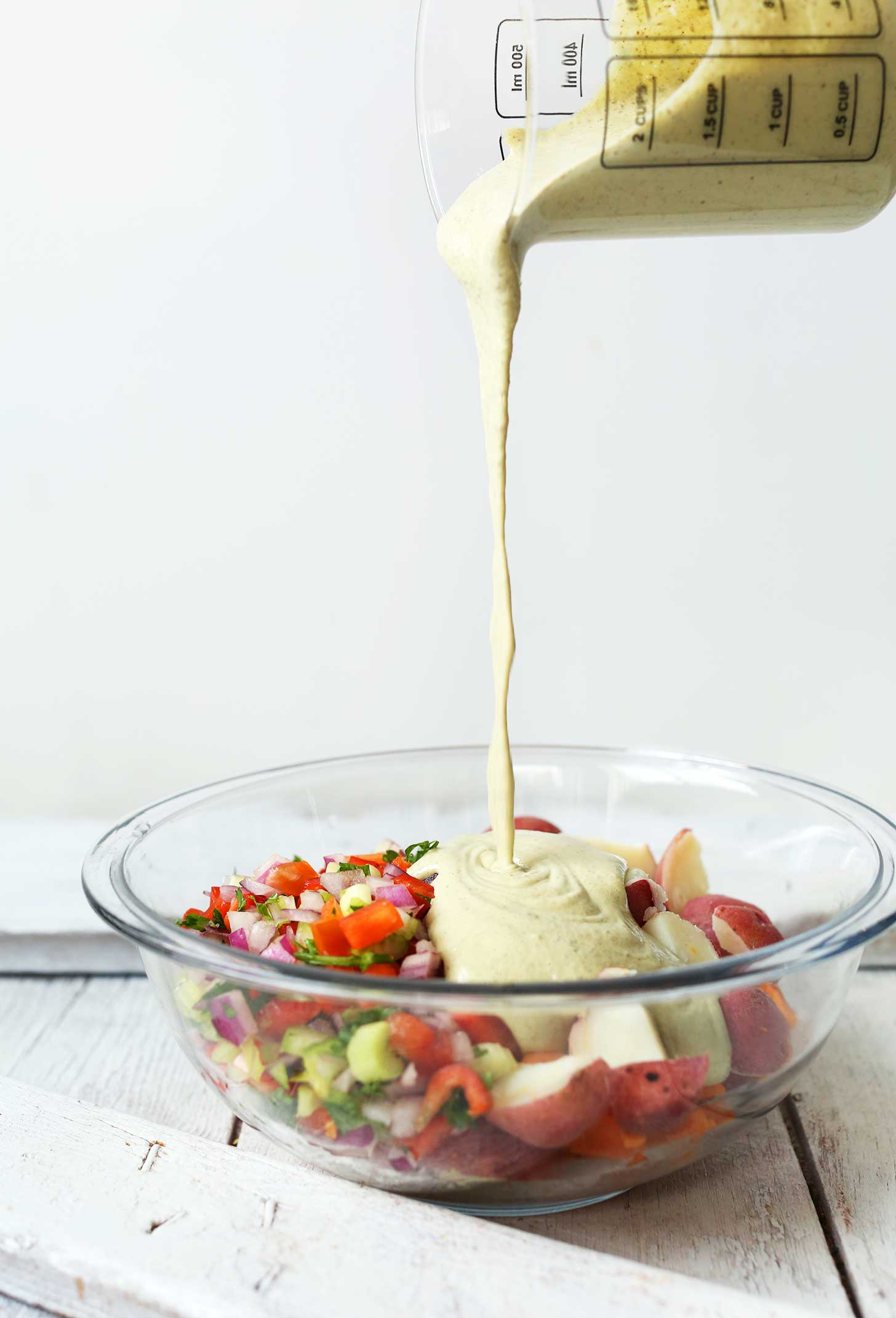 Pouring dressing onto a bowl of our Simple Vegan Potato Salad recipe