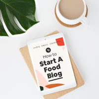 A cup of coffee sitting next to an ipad resting on a wooden block with first page of the email course How to Start A Food Blog by Minimalist Baker