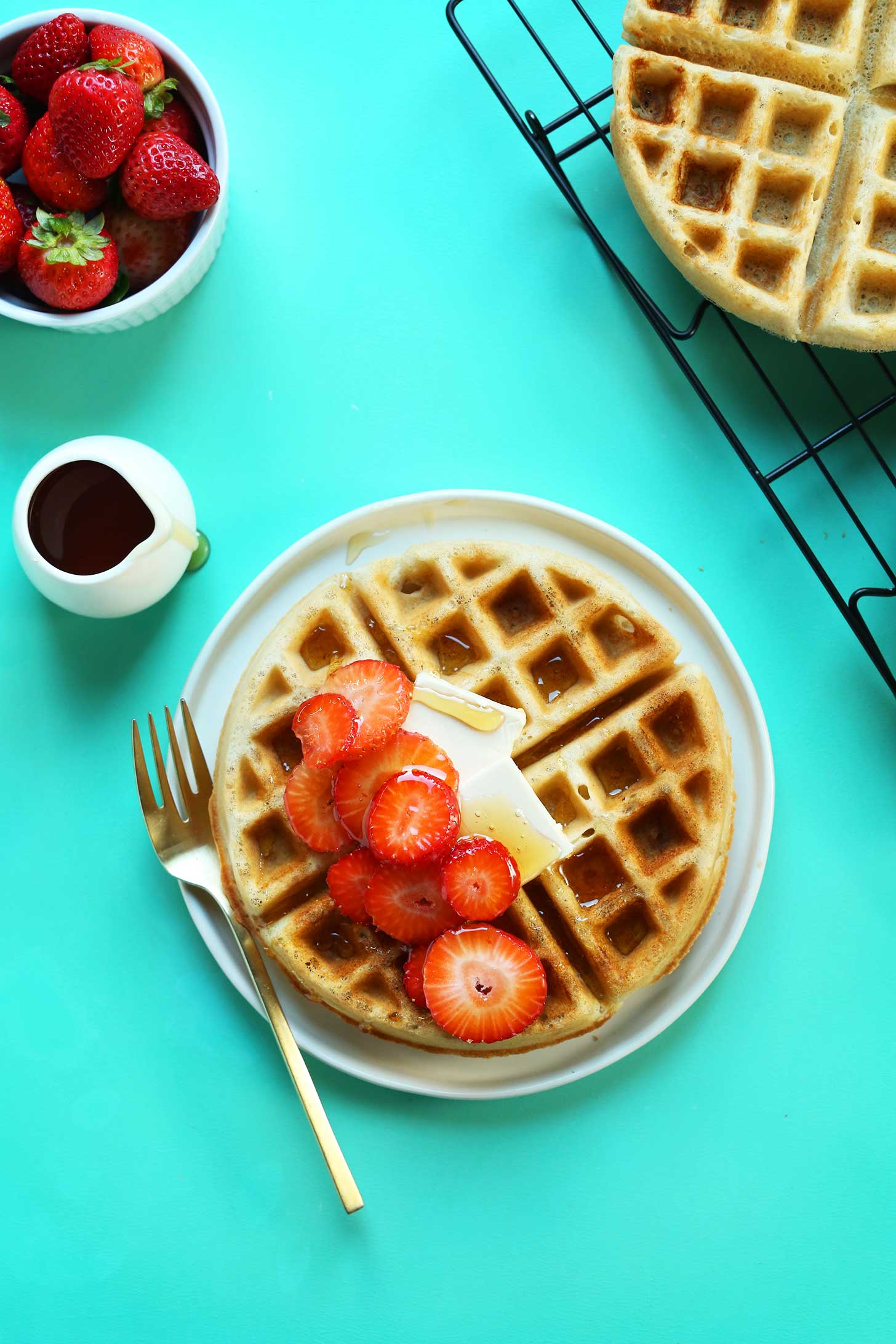 Plate with the perfect Vegan Gluten-Free Waffle topped with syrup, vegan butter, and fresh strawberries