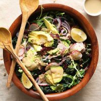 Wooden serving spoons resting on a bowl of Detox Salad