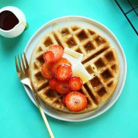 Plate with a Gluten-Free Vegan Belgian Waffle topped with sliced strawberries, vegan butter, and syrup