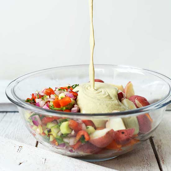 Pouring dressing into a glass bowl of our Vegan Potato Salad recipe