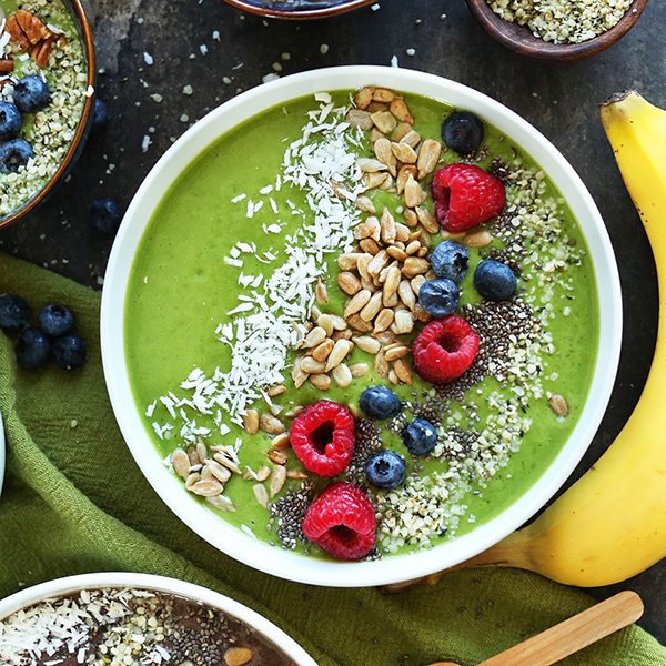 Banana, hemp seeds, and bowl of Green Smoothie Bowls topped with nuts, seeds, and berries