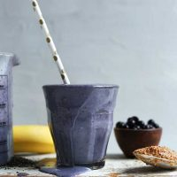 Overflowing glass of our Blueberry Almond Butter Smoothie recipe