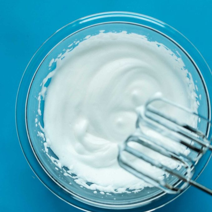 Electric mixer blades over a bowl of freshly whipped aquafaba