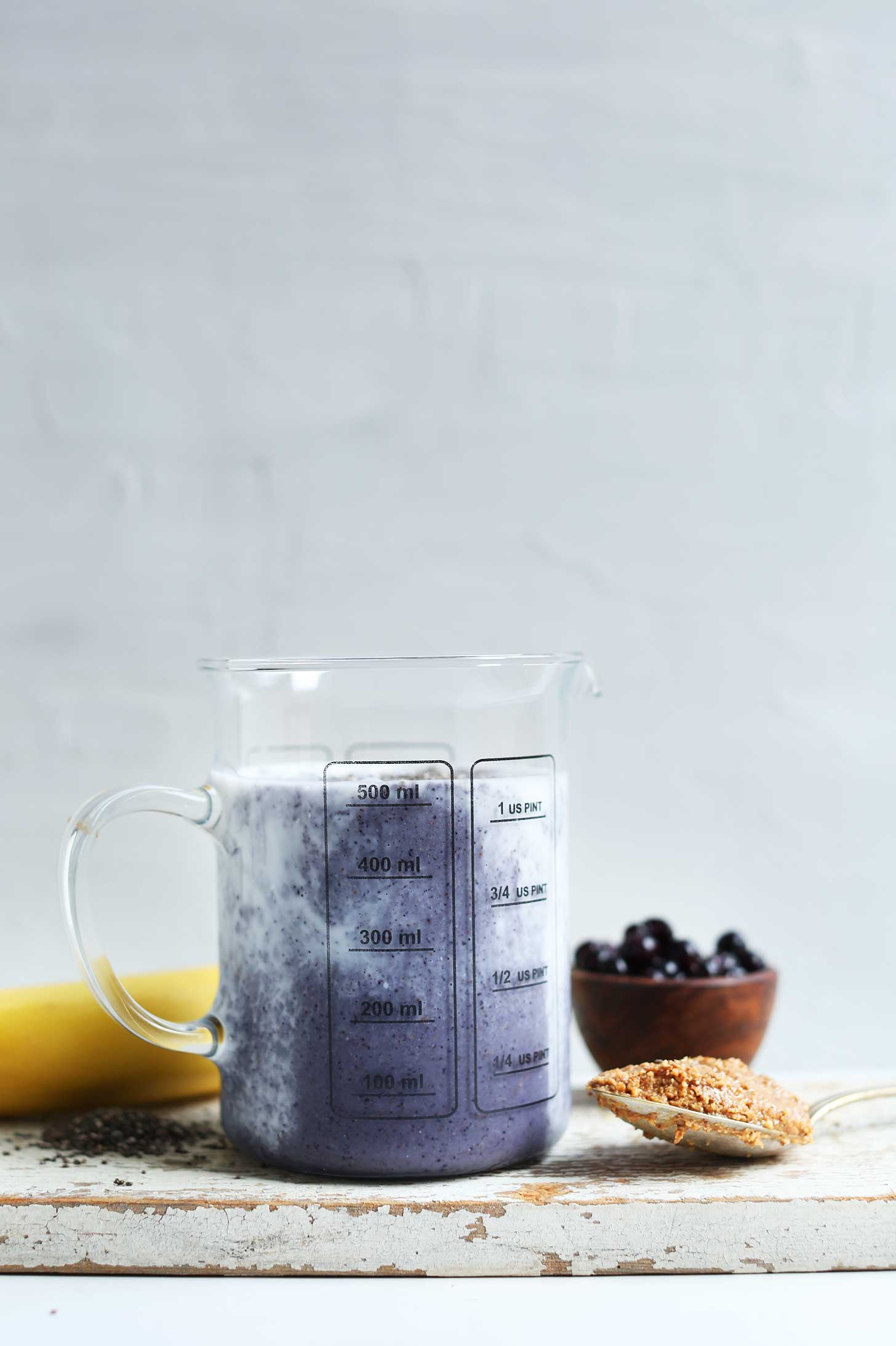 Glass measuring jar filled with creamy vegan Almond Butter Blueberry Smoothie
