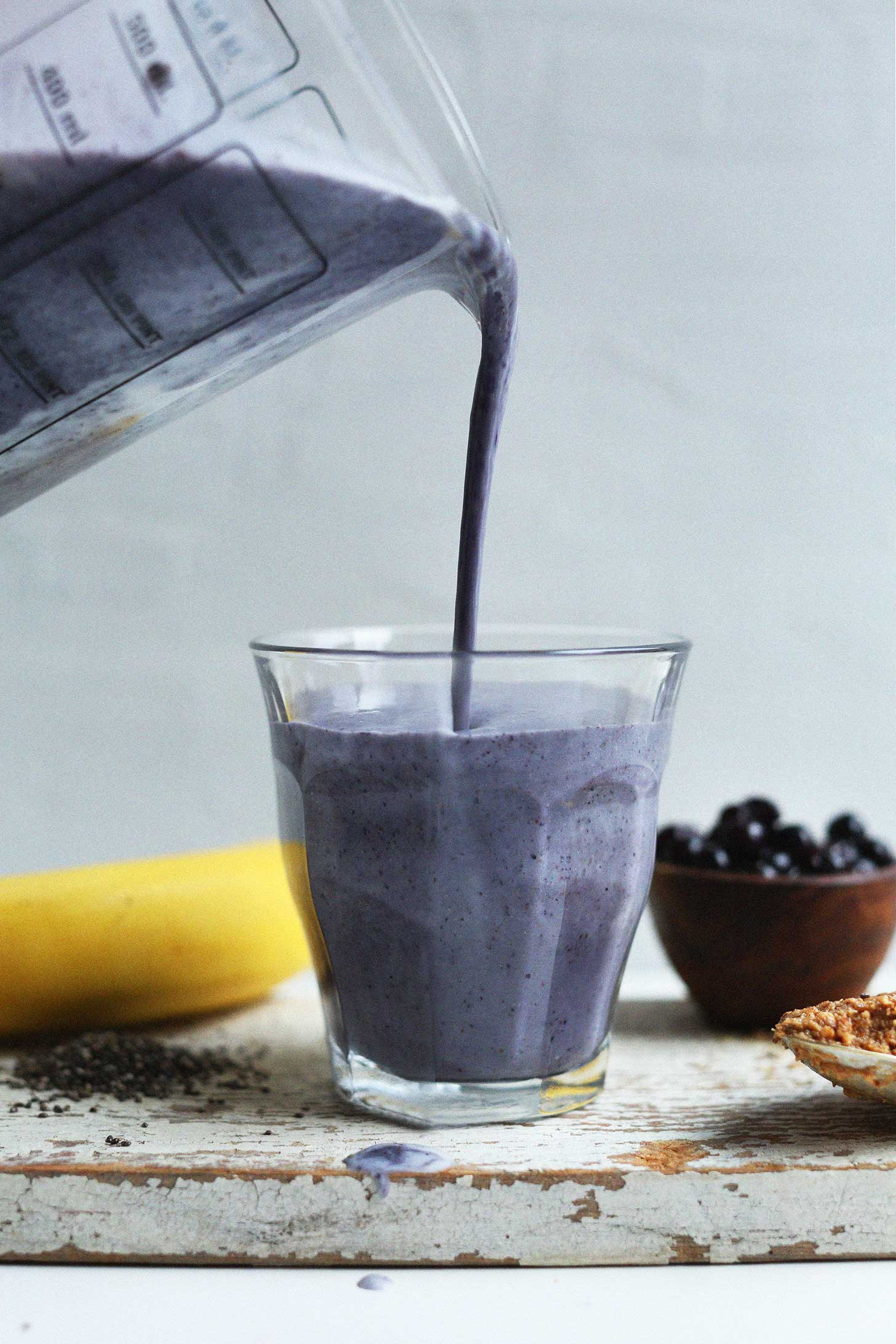 Pouring Almond Butter Blueberry Smoothie into a glass for a plant-based breakfast