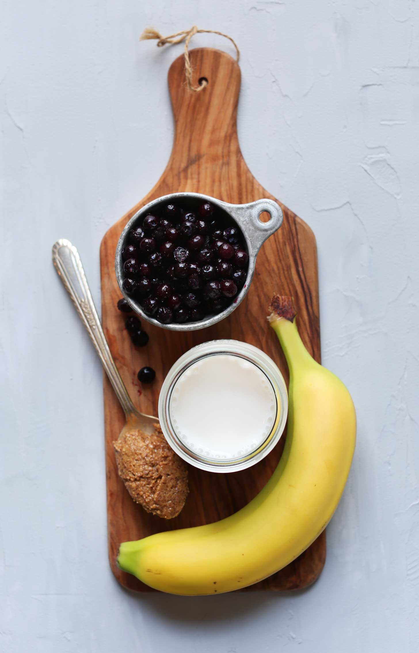 Wood board with blueberries, almond milk, almond butter, and banana for making a delicious vegan smoothie recipe