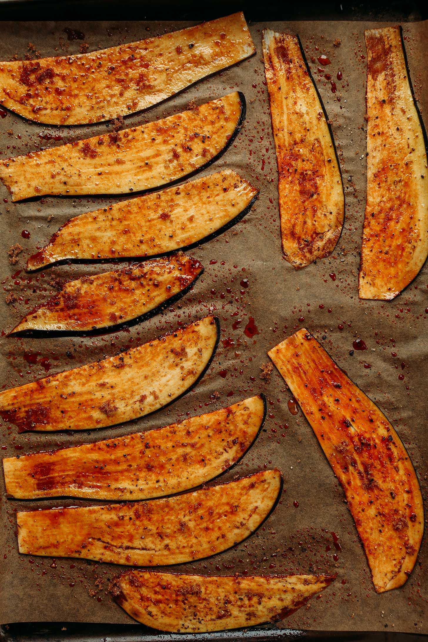 Smoky vegan Eggplant Bacon slices on a parchment-lined baking sheet